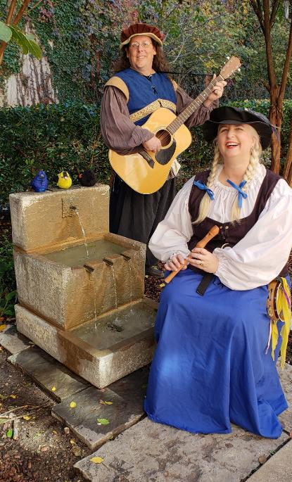 Fergus and Winifred posing by a small fountain. Winifred is sitting beside the fountain holding a recorder. Fergus is standing behind her with his guitar. They are both dressed in blue renaissance garb. Three plush birds are sitting on top of the fountain.