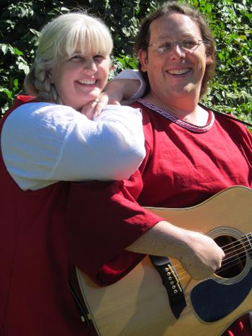 Fergus and Winifred pose for a photo. Winifred is resting her chin on her hands, which are on Fergus's shoulder. Fergus is holding his guitar, ready to begin playing. Both are smiling, and dressed in their red celtic garb.
